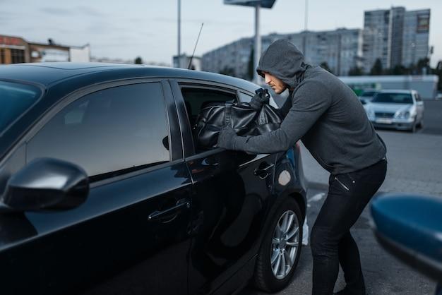 Угон автомобиля взлом двери, преступная работа, грабитель, угон. мужчина-грабитель в капюшоне открывает автомобиль на стоянке. автомобильное ограбление, автомобильное преступление
