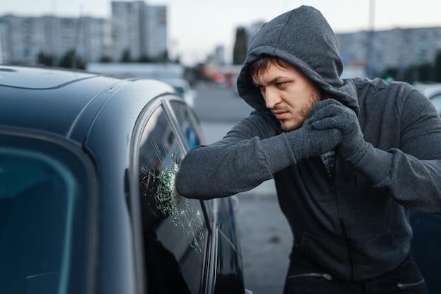 Угонщик разбивает дверное стекло, преступная работа, грабитель. мужчина-грабитель в капюшоне открывает автомобиль на стоянке. автомобильные ограбления, автомобильные преступления, вандализм