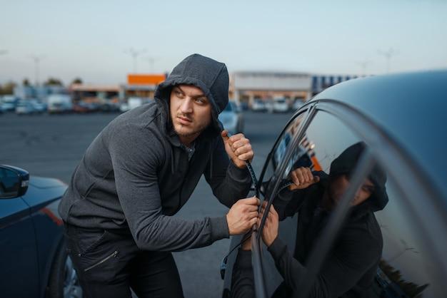 Угонщик взломал дверной замок, преступная работа, грабитель. мужчина-грабитель в капюшоне открывает автомобиль на стоянке. автомобильные ограбления, автомобильные преступления, вандализм