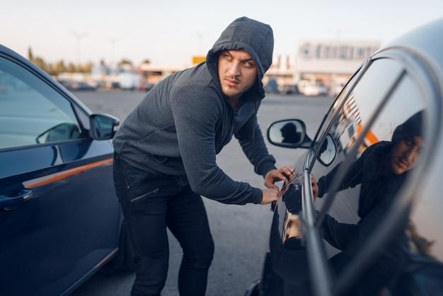 Угонщик взломал дверной замок, преступный образ жизни. мужчина-грабитель в капюшоне открывает автомобиль на стоянке. автомобильное ограбление, автомобильное преступление