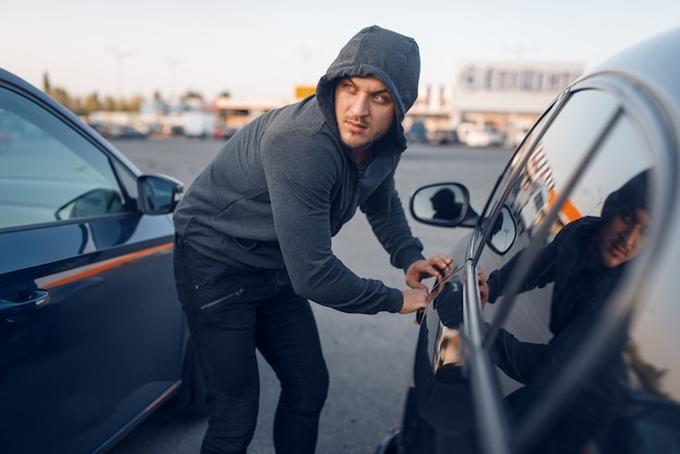 Car thief breaking door lock, criminal lifestyle. hooded male robber opening vehicle on parking. auto robbery, automobile crime
