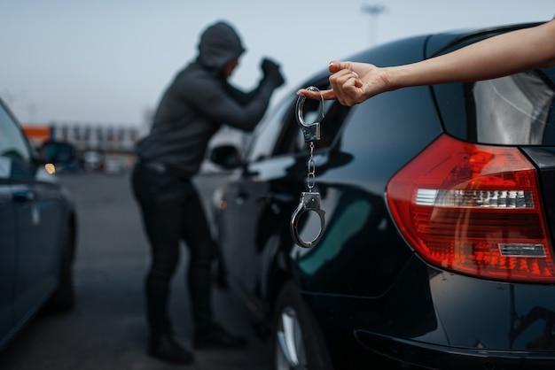 Угонщик взломал дверной замок, преступный образ жизни, нелегальная работа, грабитель. грабитель с капюшоном открывает автомобиль на стоянке, женская рука с наручниками. автомобильные ограбления, автомобильные преступления, вандализм