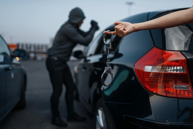 Car thief breaking door lock, criminal lifestyle, illegal work, burglar. hooded male robber opening vehicle on parking, female hand with handcuff. auto robbery, automobile crime, vandalism