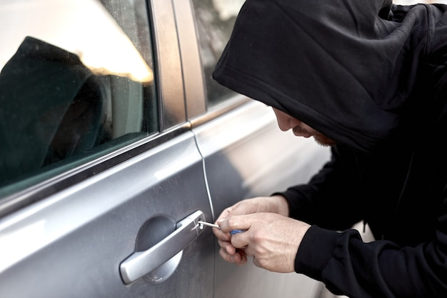 Car thief steal car breaking door criminal job burglar hijacks auto thief in black wear