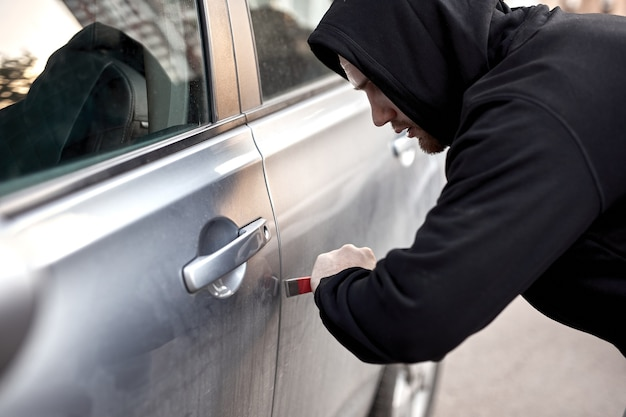Угонщик угоняет машину, ломая дверь, преступная работа, грабитель угоняет авто вор в черной одежде