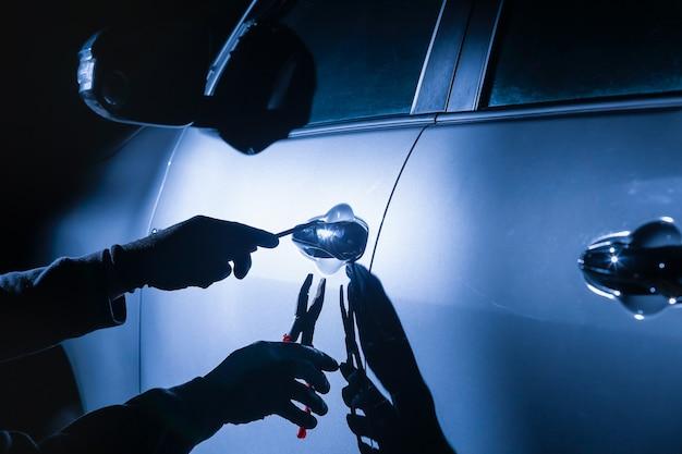 ツールを使用して車に侵入する車泥棒