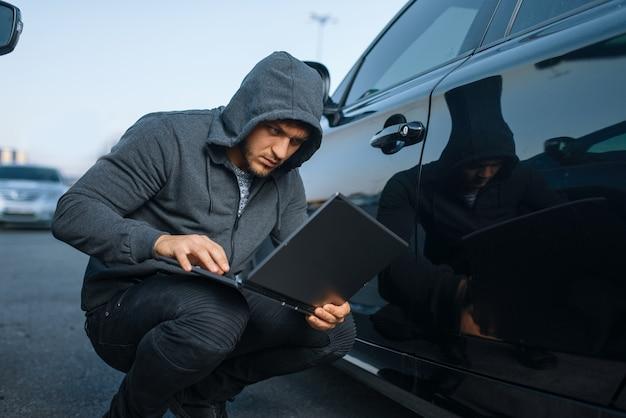 Угонщик с системой сигнализации взлома ноутбука, преступный образ жизни. мужчина-грабитель в капюшоне открывает автомобиль на стоянке. автомобильное ограбление, автомобильное преступление