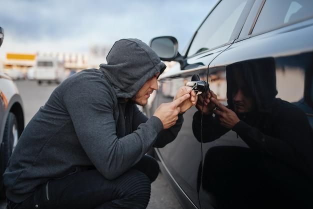 Угонщик с отверткой взламывает дверной замок. мужчина-грабитель в капюшоне открывает автомобиль на стоянке. автомобильное ограбление, автомобильное преступление