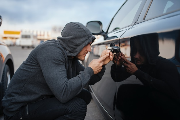 Car thief with screwdriver breaking door lock. hooded male robber opening vehicle on parking. auto robbery, automobile crime