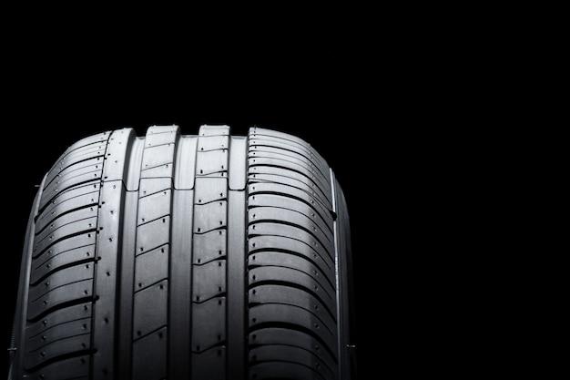 Автомобильная шина на черном