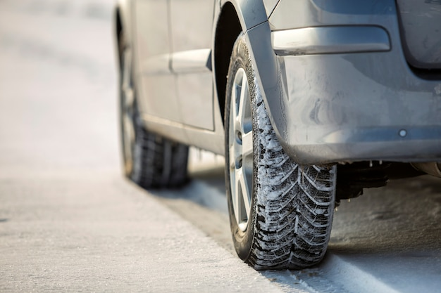 Car tire parked on snowy road on winter day. transportation and safety concept.