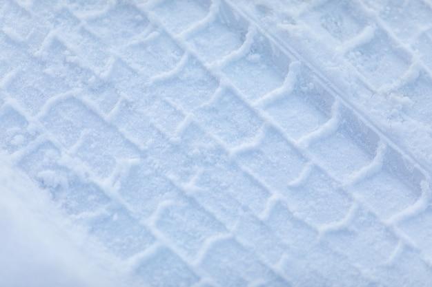 雪の上の車のタイヤのプリントをクローズアップ