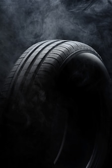 Car tire and smoke on black