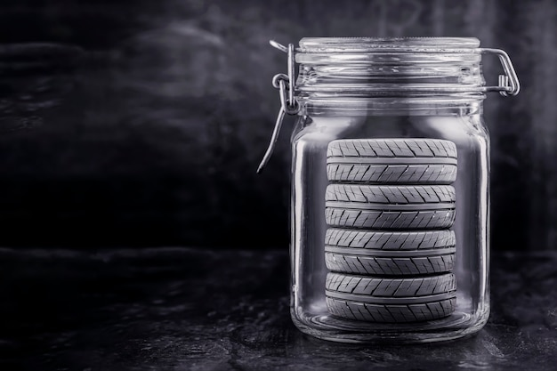 Car tire storage service. wheels are stored in a glass jar, concept. copy space, black background.