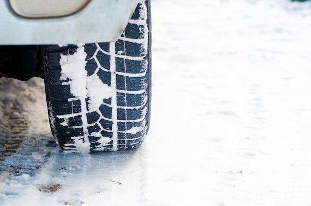 Автомобильные шины на зимней дороге покрыты снегом. транспортное средство на заснеженной аллее утром при снегопаде