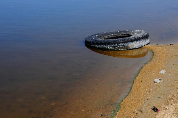 Car tires on the shore hadzhibeysky estuary. eutrophication of the reservoir, the problem of ecology