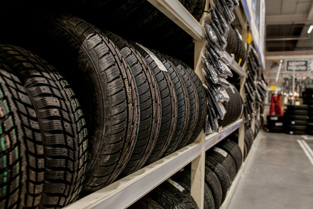Car tires and wheels at warehouse in tire store.