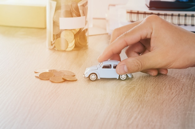 Car toy in the men hand on desk with blured money coin in jar bank saving,warm tone filter
