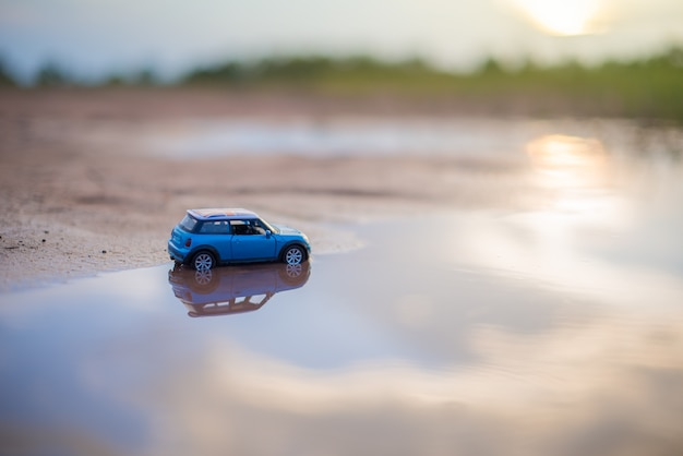 Car toy models are on the water reflection with sunlight blurry background