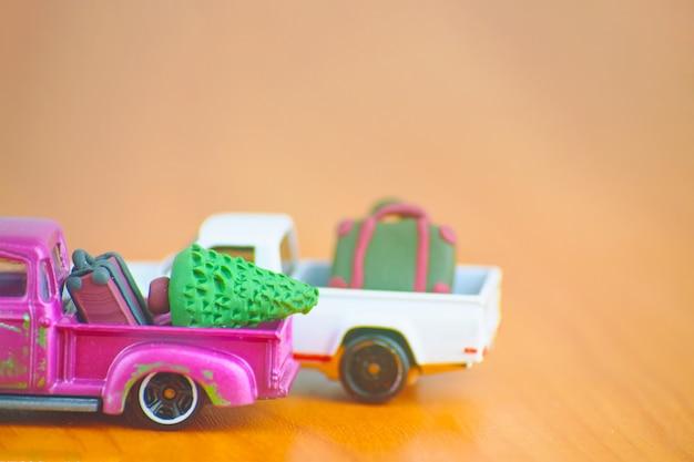 여행 가방과 크리스마스 트리 미니어처 전나무와 폴리머 클레이로 만든 서류 가방이 있는 자동차 장난감 모델...