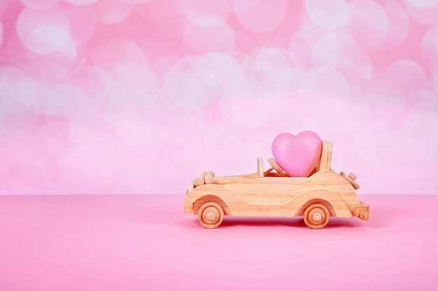 Car toy with a gift and a bow in the form of a heart on a pink background with bokeh
