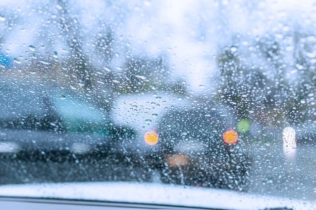젖은 앞유리를 통해 유리에 많은 빗방울이 보이는 비오는 날의 자동차 교통