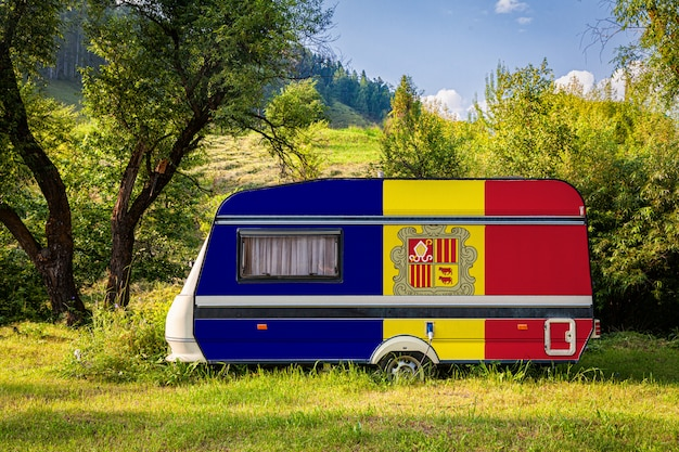 A car trailer, a motor home, painted in the national flag of andorra stands parked in a mountainous.