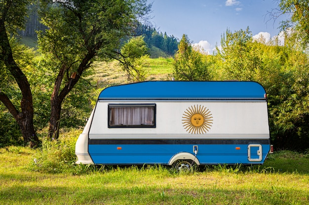 A car trailer, a motor home, painted in the national flag of argentina stands parked in a mountainous.