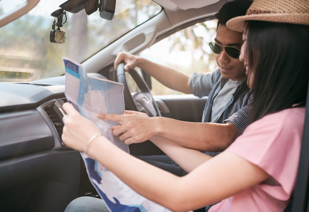 Car travel and road trip. couple in car with map.