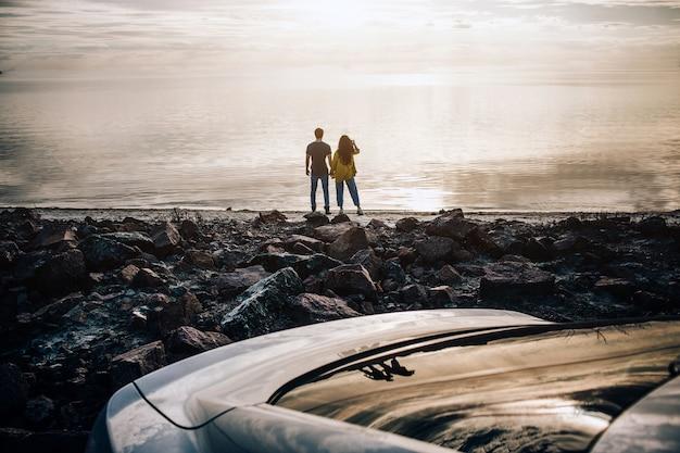 車での旅行、観光-楽しみ、観光でのリラクゼーション、旅行、自由時間、休息、幸福の概念。海岸近くのカップルのシルエット。