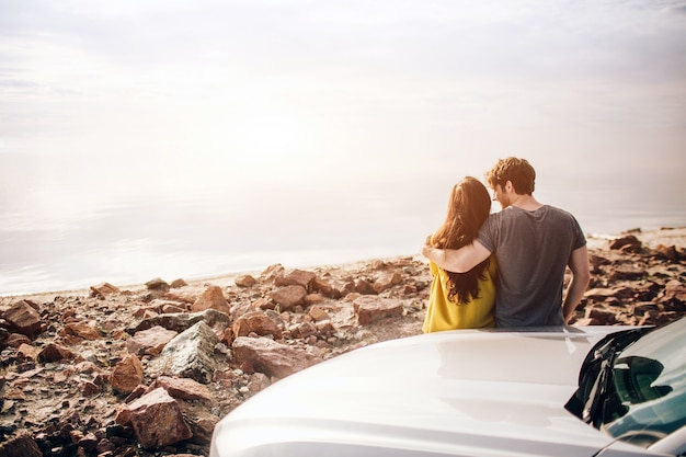 車の旅行、観光-スポーツカーの夕日に田舎道を運転する幸せなカップル