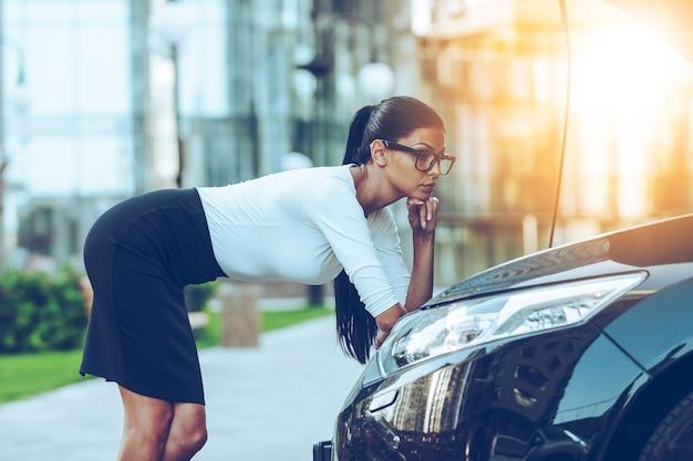 Проблемы с автомобилем. соблазнительная молодая бизнесвумен, взявшись за подбородок, опираясь на открытый капот своего автомобиля