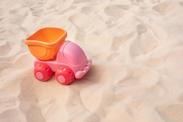 車、砂の上のトラックのおもちゃ、ビーチの夏と学習の概念