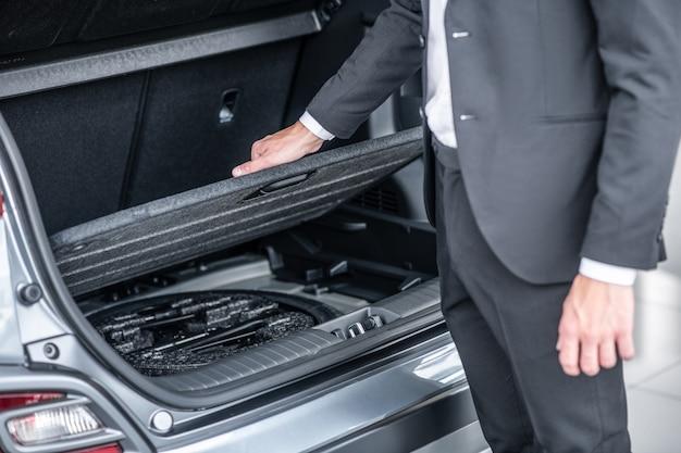 Автомобильный багажник. мужчина в темном деловом костюме стоит возле открытого багажника автомобиля, проверяя вместительность и удобство, лица не видно