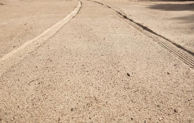遠近法でビーチの砂の上の車のタイヤのトラック