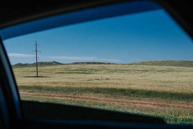 경치 좋은 시골, 마른 풀이 무성한 대초원, 멀리 언덕의 자동차 전망. 경로와 평행하게 달리는 지상 트랙.