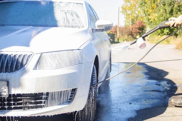 洗車。洗車。男は車を洗う。フォーム