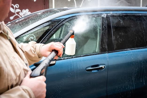 洗車プロセス。車の表面にフォームバブルシャンプーをスプレーします。