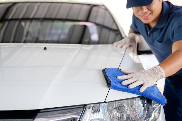 Персонал автомойки чистит свои машины салфетками из микрофибры. детали и концепция камердинера выборочный фокус вид крупным планом