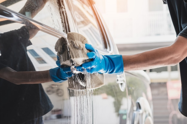 Персонал автомойки в синих резиновых перчатках с помощью губки, смоченной водой с мылом, для очистки автомобиля.