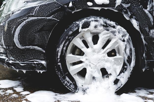 활성 거품 비누로 세차. 휠 타이어 청소. 상업용 청소 서비스 개념입니다.