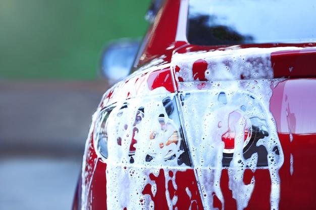 Концепция мойки автомобилей. красная машина в пене