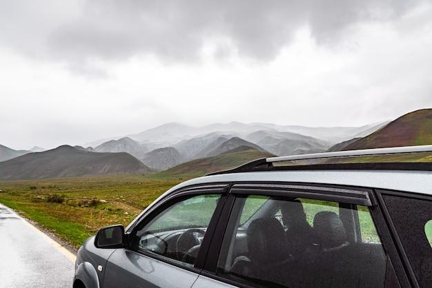 Car on wet asphalt road in mountainous area