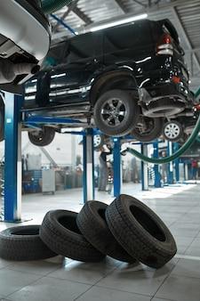 자동차 바퀴와 리프트, 타이어 서비스 개념, 아무도. 차량 수리 차고, 전문 자동차 검사, 자동 스테이션 내부, 고품질 부품 및 소모품