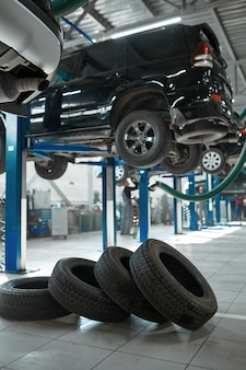 Car wheel and auto on lift, tire service concept, nobody. vehicle repairing garage, professional automobile inspection, auto station interior, high-quality parts and consumables