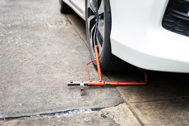 Car wheel blocked by red wheel lock because of illegal parking violation
