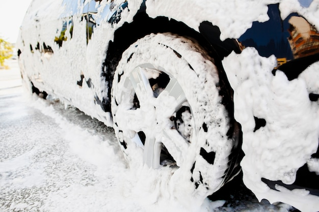 Car wheel covered in soap foam