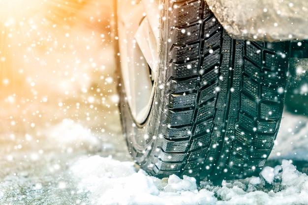 Колесо автомобиля на заснеженной дороге и снежинки