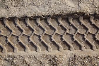 車のホイールはビーチの砂の上の足跡をティアレス