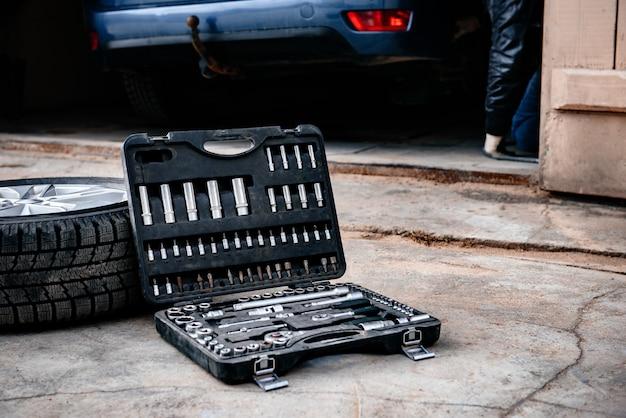 Колесо автомобиля с ящиком для инструментов на фоне асфальта.